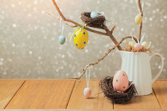 Easter holiday decorations on wooden table over bokeh background Stock Photo