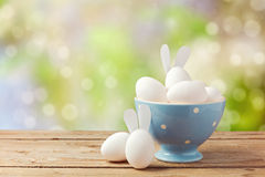 Easter holiday eggs with bunny ears on wooden table over garden bokeh background