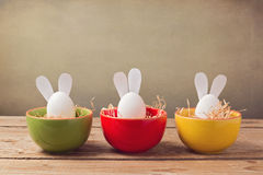 Easter holiday eggs with bunny ears on wooden table Royalty Free Stock Images