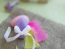 Painted egg with bowknot, colorful feathers on burlap fabric background. Easter holiday greeting concept. Painted egg with bowknot, colorful feathers on burlap stock photography