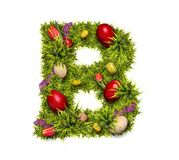 Easter holiday letter B. Made of fresh green grass and Easter eggs isolated on white background stock image