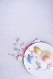 Easter holiday pastel decorations. Colorful eggs, sweet dessert, bunny ears. Top view, copy space. Stock Photos