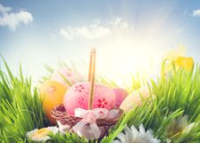 Easter holiday scene background. Traditional painted colorful eggs in spring grass over blue sky royalty free stock photos