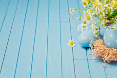 Easter holiday wooden background with daisy flowers and painted eggs Stock Photos