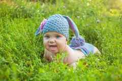 Easter holidays! Cute baby in a Easter bunny of lamb costume. In the green spring grass. Smiling baby kid posing like an Easter bunny. Children have fun royalty free stock photos