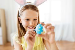 Happy girl coloring easter eggs at home stock images