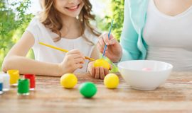 Happy smiling girl and mother coloring easter eggs royalty free stock images