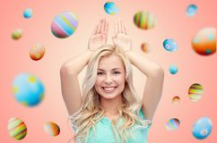Happy smiling young woman making easter bunny ears. Easter, holidays and people concept - happy smiling young woman making bunny ears over pink or living coral stock photography