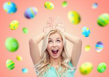 Happy smiling young woman making easter bunny ears stock photo