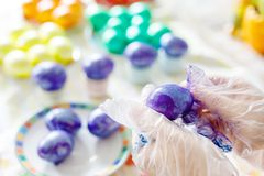 Close-up of adult hands coloring Easter eggs with colors Royalty Free Stock Photo