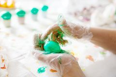 Close-up of adult hands coloring Easter eggs with colors Stock Photography