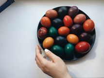 Easter, holidays, tradition and people concept. Close up of Caucasian woman`s hands holding easter eggs with colors stock photo