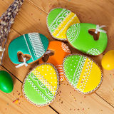 Easter homemade gingerbread cookie and eggs over wooden table Royalty Free Stock Image