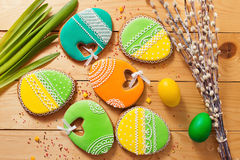 Easter homemade gingerbread cookie and eggs over wooden table Stock Photo