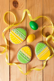 Easter homemade gingerbread cookie and eggs over wooden table Royalty Free Stock Photo