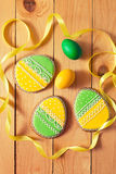 Easter homemade gingerbread cookie and eggs over wooden table Royalty Free Stock Photos