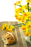 Easter hot cross bun. Easter hot cross bun with yellow narcissus Royalty Free Stock Photo