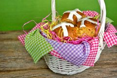 Easter hot cross buns. Fresh homemade hot cross buns in a white wicker basket with colorful gingham fabric Stock Photos