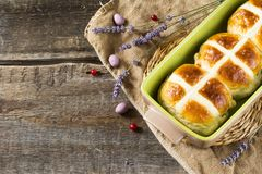 Easter hot cross buns with lavender flowers, chocolate eggs and cranberry on bag and wooden table. Easter bakery Royalty Free Stock Photo