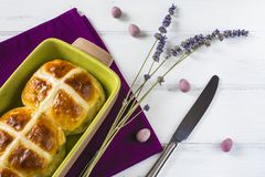 Easter hot cross buns with lavender flowers, chocolate eggs and knife on napkin and wooden white table. Traditional Easter hot cross buns with lavender flowers Royalty Free Stock Photos