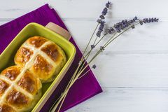 Easter hot cross buns with lavender flowers on napkin and wooden white table. Traditional Easter hot cross buns with lavender flowers on napkin and wooden white Royalty Free Stock Image