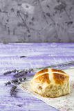 Easter hot cross buns with lavender flowers on napkin and wooden white and violet table. Easter baking Royalty Free Stock Images