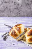 Easter hot cross buns with lavender flowers on napkin and wooden white and violet table. Easter baking Royalty Free Stock Photography