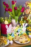 Easter Hot Cross Buns. Selection of Easter Hot Cross Buns with chocolate Easter Eggs and spring flowers with novelty chicks stock image