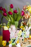 Easter Hot Cross Buns. Selection of Easter Hot Cross Buns with chocolate Easter Eggs and spring flowers with novelty chicks royalty free stock images