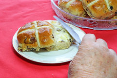 Easter hot cross buns. Spreading butter on bun. Royalty Free Stock Photo