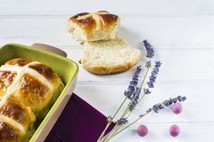 Easter hot cross buns witt lavender flower, and chocolate eggs on violet napkin and wooden white table. Easter baking Royalty Free Stock Image