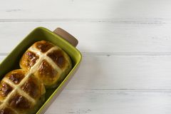 Easter hot cross buns on wooden white table. Traditional Easter hot cross buns on wooden white table. 2 yeast buns Stock Photo