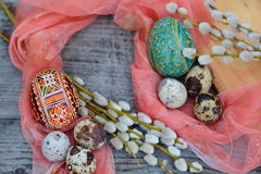 Easter installation - handmade easter eggs, quail eggs and willow. On wooden background Stock Image
