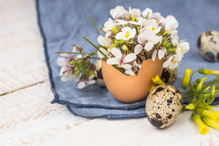 Easter interior decoration, bouquet of white flowers in eggshell, quail eggs, blue linen napkin. On wood table, close up Royalty Free Stock Photo