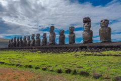 Easter Island Moai Statues. Wide angle shot of 15 Moai statues facing inward over Easter Island at Tongariki with a dramatic white cloud and blue sky background Royalty Free Stock Photos