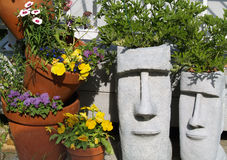 Easter Island Planters 1. Two Easter Island garden planters next to some other clay planter pots with plants in all Royalty Free Stock Photos