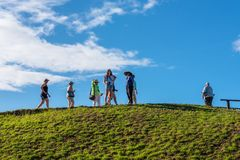 Easter Island Tourists Gather at the Top of a Hill. Easter Island, Chile -- March 31, 2018. Tourists stand at the top of a hill on Easter Island in the South royalty free stock photos