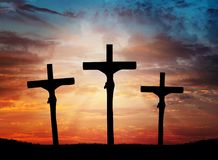 Easter, Jesus Christ cross dramatic sky, lighting. Dramatic orange, red sunset sky, light rays, sunbeams behind the three crosses silhouettes. and dark clouds stock photography