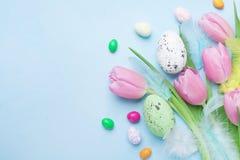 easter karciany powitanie Tulipanowi kwiaty, jajka i cukierek na błękitnym stołowym odgórnym widoku, Obraz Royalty Free
