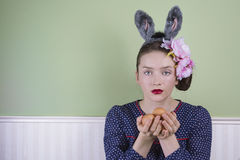 Easter lady holding eggs. Portrait of a young woman holding a few eggs in her hands and wearing bunny ears Stock Photo