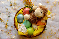 Easter lamb with colored pearly eggs in basket stock photos