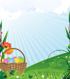 Easter landscape. Basket with Easter eggs on a green meadow Royalty Free Stock Images