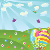 Easter landscape. Easter eggs on a sunny field Royalty Free Stock Images