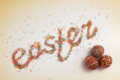 Easter lettering made from colorful baking sugar and colorful hand drawn eggs Royalty Free Stock Images