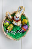 Easter Letters, Chocolate Bunnies and Eggs in a Basket Royalty Free Stock Images