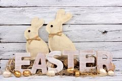 Easter letters with eggs and bunnies against rustic white wood. Wooden Easter letters with eggs and bunnies against a rustic white wood background Royalty Free Stock Image