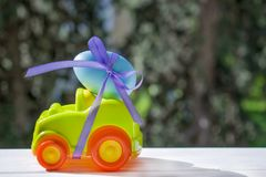 Easter light green car with a blue egg. Tied with a purple ribbon rides on the table against the background of greenery stock images