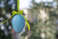 Easter light green car with a blue egg. Tied with a purple ribbon rides on the table against the background of greenery royalty free stock images