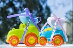 Easter light green car with a blue egg. Two Easter cars tied up with colored ribbons go on the table on the background of greenery stock photos