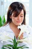 Easter Lily Plant. Beautiful Brunette Young Woman Smelling The Perfum From An Easter Lily Royalty Free Stock Photography